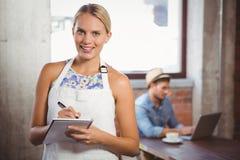 Lächelnde blonde Kellnerin, die Bestellung vor Kunden entgegennimmt Stockfotos