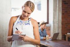 Lächelnde blonde Kellnerin, die Bestellung vor Kunden entgegennimmt Lizenzfreies Stockbild