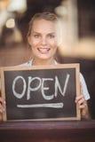 Lächelnde blonde Kellnerin, die Tafel mit offenem Zeichen zeigt Stockfotografie