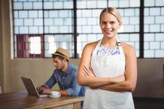 Lächelnde blonde Kellnerin, die vor Kunden aufwirft Stockbild