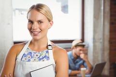 Lächelnde blonde Kellnerin, die vor Kunden aufwirft Stockfotos