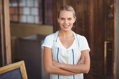 Lächelnde blonde Kellnerin mit den Armen gekreuzt Lizenzfreies Stockfoto