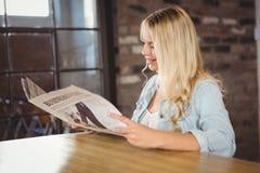 Lächelnde blonde Lesezeitung Lizenzfreie Stockbilder