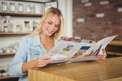 Lächelnde blonde Lesezeitung Stockbilder