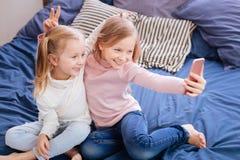 Lächelnde blonde Mädchen, die Häschenohren herstellen Lizenzfreie Stockbilder
