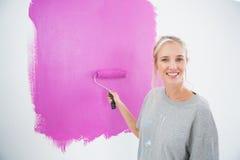 Lächelnde blonde Malerei ihr Wandrosa Stockbild