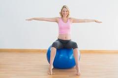 Lächelnde blonde schwangere Frau, die auf Übungsball sitzt Stockfoto