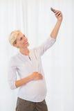 Lächelnde blonde schwangere Frau, die ein selfie nimmt Lizenzfreies Stockfoto
