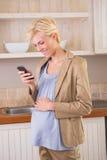 Lächelnde blonde Schwangerschaft unter Verwendung des Telefons Lizenzfreies Stockfoto