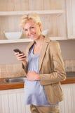 Lächelnde blonde Schwangerschaft unter Verwendung seines Telefons Stockfotografie