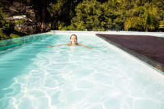 Lächelnde blonde Schwimmen im Pool Lizenzfreie Stockfotos