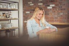 Lächelnde blonde Sitzen- und Holdingmitnehmerschale Stockfotos