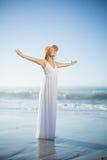 Lächelnde blonde Stellung auf dem Strand in den weißen sundress und im sunhat Lizenzfreie Stockfotos