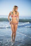 Lächelnde blonde Stellung auf dem Strand im Bikini Stockfotos