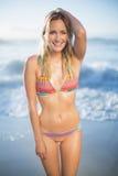 Lächelnde blonde Stellung auf dem Strand im Bikini Stockbild
