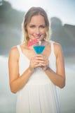 Lächelnde blonde Stellung am Strand in den weißen sundress mit blauem Cocktail Stockfoto