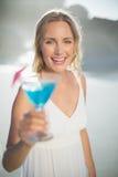 Lächelnde blonde Stellung am Strand in den weißen sundress mit blauem Cocktail Stockbild