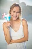 Lächelnde blonde Stellung am Strand in den weißen sundress mit blauem Cocktail Lizenzfreies Stockfoto