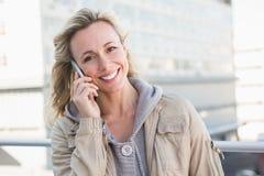 Lächelnde blonde Stellung am Telefon Stockfoto
