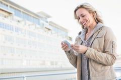 Lächelnde blonde Stellung und Versenden von SMS-Nachrichten Stockbild
