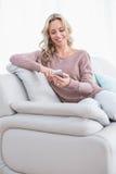 Lächelnde blonde Versenden von SMS-Nachrichten auf der Couch Lizenzfreie Stockfotos