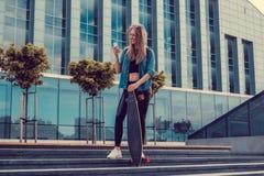Lächelnde blonde weibliche Aufstellung auf Schritten Stockbild