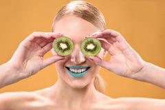 Lächelnde blonde weibliche Aufstellung mit Kiwi Lizenzfreie Stockbilder