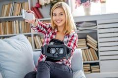 Lächelnde blonde weibliche darstellende Gläser der virtuellen Realität Lizenzfreies Stockbild