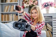 Lächelnde blonde weibliche darstellende Gläser der virtuellen Realität Stockfoto