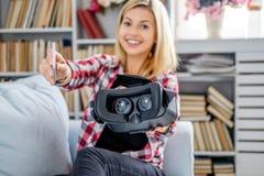Lächelnde blonde weibliche darstellende Gläser der virtuellen Realität Lizenzfreie Stockfotografie