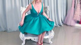 Lächelnde blonde weibliche Länder auf dem Lehnsessel im Bekleidungsgeschäft, entspannend nach dem erfolgreichen Einkaufen stock video