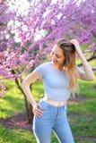 Lächelnde blonde weibliche Person, die im Park mit Blütenhintergrund steht Stockfoto