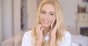 Lächelnde blonde weibliche Unterhaltung durch Telefon Stockbilder