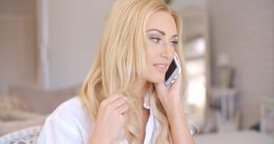Lächelnde blonde weibliche Unterhaltung durch Telefon Stockfotografie