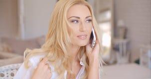Lächelnde blonde weibliche Unterhaltung durch Telefon Lizenzfreie Stockfotografie