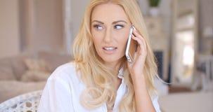 Lächelnde blonde weibliche Unterhaltung durch Telefon Lizenzfreie Stockfotos