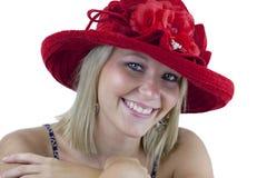 Lächelnde Blondine im roten Hut getrennt Stockfotografie