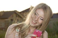 Lächelnde Blondine im windigen Wetter Stockfotografie