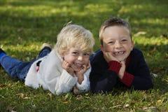 Lächelnde Brüder, die in das Gras legen Lizenzfreie Stockfotos
