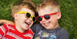 Lächelnde Brüder, die fantastische Sonnenbrille tragen Stockfotografie