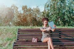 Lächelnde brasilianische Frau mit digitaler Tablette in einem allgemeinen Garten stockfotografie