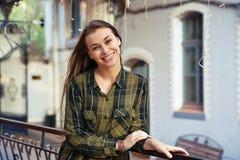 Lächelnde braunhaarige Frau lehnt sich auf dem Geländer Stockbilder