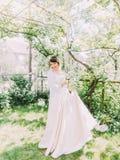 Lächelnde Braut mit dem Hochzeitskleid verbringt Zeit im sonnigen Garten Lizenzfreies Stockbild