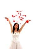 Lächelnde Braut wirft rosafarbene Blumenblätter Stockfotos