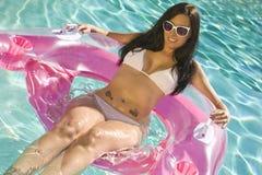 Lächelnde Brunette-Frau, die in einem Pool-Stuhl sitzt Lizenzfreies Stockbild