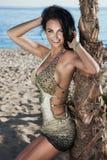 Lächelnde Brunettedame, die am Strand aufwirft. Lizenzfreies Stockbild
