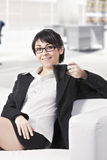 Lächelnde Brunettefrau auf Sofa im Büro Stockbilder