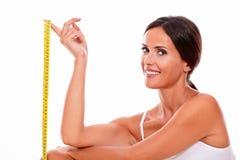 Lächelnde Brunettefrau mit Maßband stockbilder