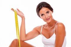 Lächelnde Brunettefrau mit Maßband lizenzfreies stockfoto