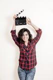 Lächelnde Brunetteschauspielerin mit Filmscharnierventilbrett oben lizenzfreie stockfotos